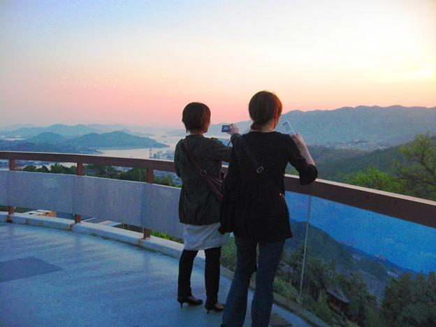 展望台から瀬戸の夕日を撮る若い二人連れ