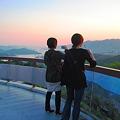 写真: 展望台から瀬戸の夕日を撮る若い二人連れ